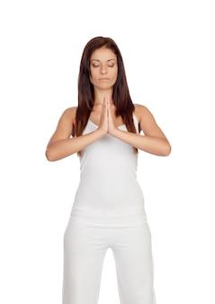 La ragazza attraente si è vestita nell'yoga di pratica bianca isolata