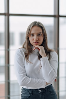 La ragazza attraente sulla finestra mostra diverse emozioni e umore.