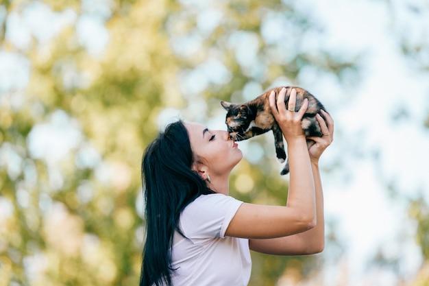La ragazza bacia il gattino in natura