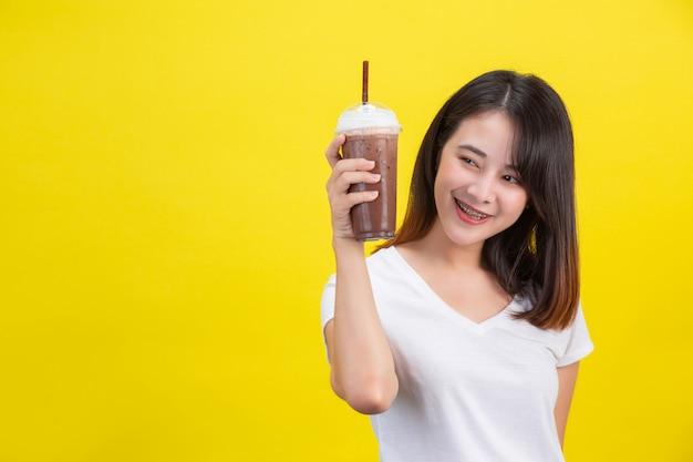 La ragazza beve acqua fredda dal cacao da un bicchiere di plastica trasparente su un giallo.
