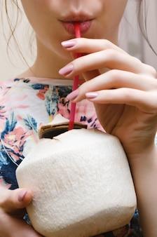 La ragazza beve il cocco giovane