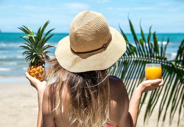La ragazza beve il succo sulla spiaggia