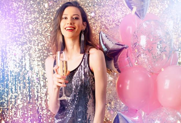 La ragazza beve vino spumante per festeggiare il nuovo anno