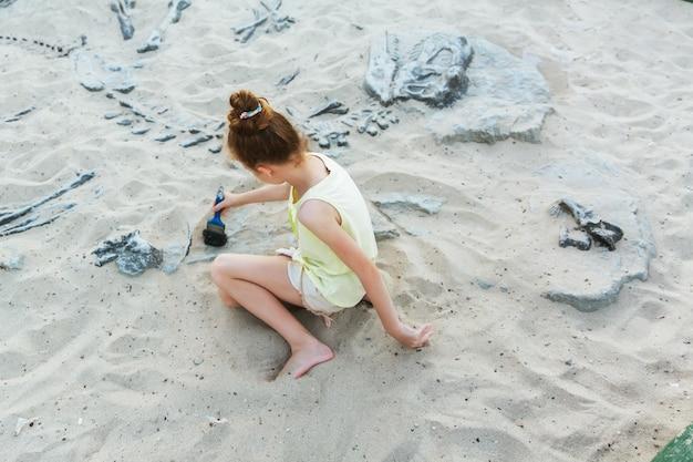 La ragazza bianca si diverte scavando nella sabbia al parco di avventura, fuoco selettivo
