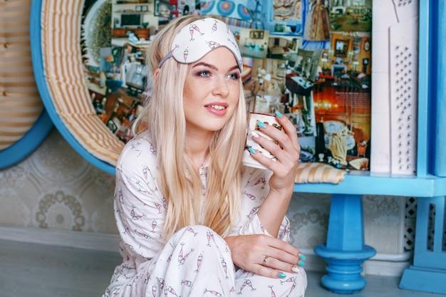 La ragazza bionda beve il caffè in un pigiama. maschera del sonno concetto l