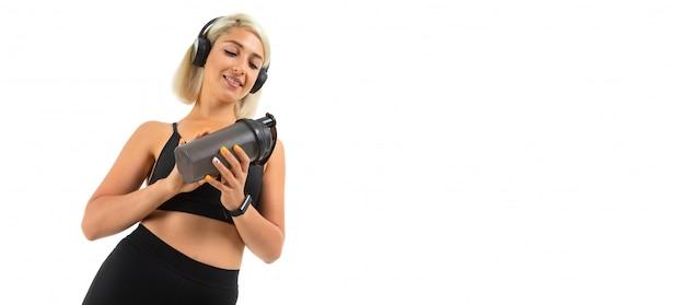 La ragazza bionda caucasica di sport sta con le cuffie fa gli sport e beve l'acqua dalla bottiglia di sport che mostra