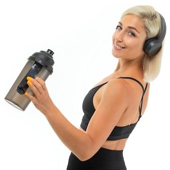 La ragazza bionda caucasica di sport sta di nuovo alla macchina fotografica con le cuffie fa gli sport e beve l'acqua dalla bottiglia di sport