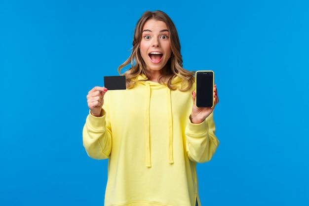 La ragazza bionda divertita ed eccitata consiglia di utilizzare il servizio bancario, mostrando il display dello smartphone e la carta di credito e guardando la fotocamera affascinata come ricevere bonus sul conto bancario,