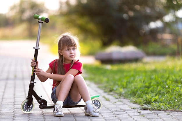 La ragazza bionda premurosa dai capelli lunghi abbastanza giovane del bambino in pantaloncini e maglietta si siede sullo scooter sull'estate vaga strada vuota vuota del sobborgo luminosa. attività per bambini, giochi e concetto divertente.