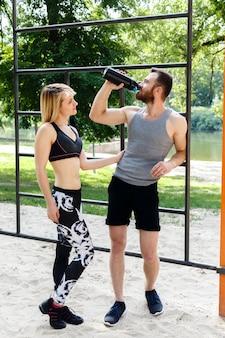 La ragazza bionda sportiva e l'uomo barbuto stanno riposando dopo l'allenamento di allenamento in un parco.