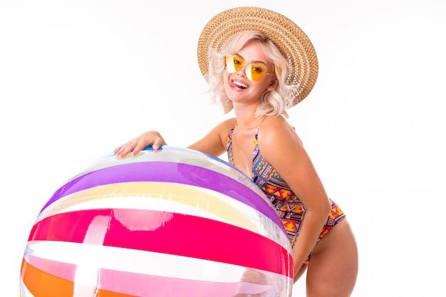 La ragazza bionda sveglia in un costume da bagno in occhiali da sole tiene una lecca-lecca e una palla da nuoto