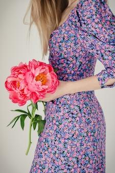 La ragazza blogger tiene in mano un bouquet di poonie rosse vestite con un abito viola con una stampa floreale su uno sfondo bianco nella stanza dal design moderno