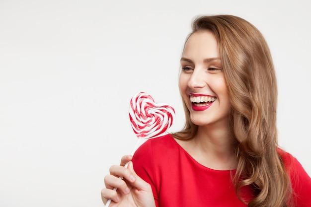 La ragazza bruna tiene in mano una lecca-lecca come un cuore e ride