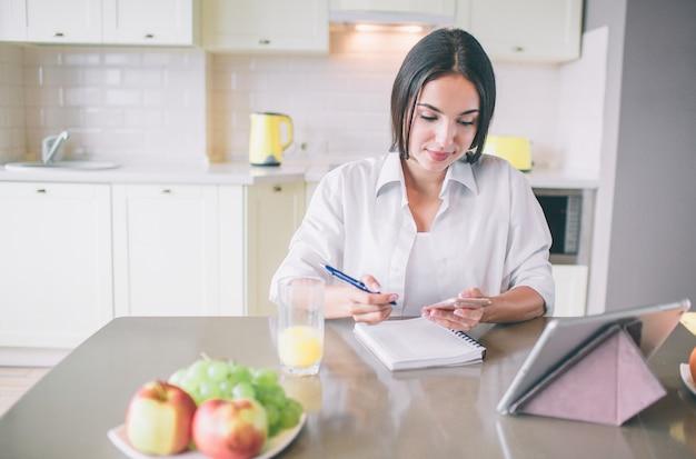 La ragazza calma e occupata si siede al tavolo e lavora.