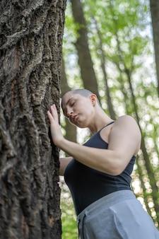 La ragazza calva medita facendo una pausa l'albero