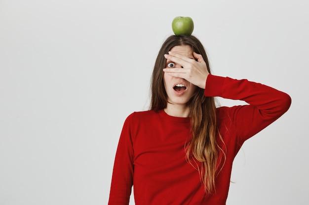 La ragazza carina in agguato si sente spaventata della sua vita, copre gli occhi, sbirciando tra le dita mentre trattiene il bersaglio verde mela sulla testa