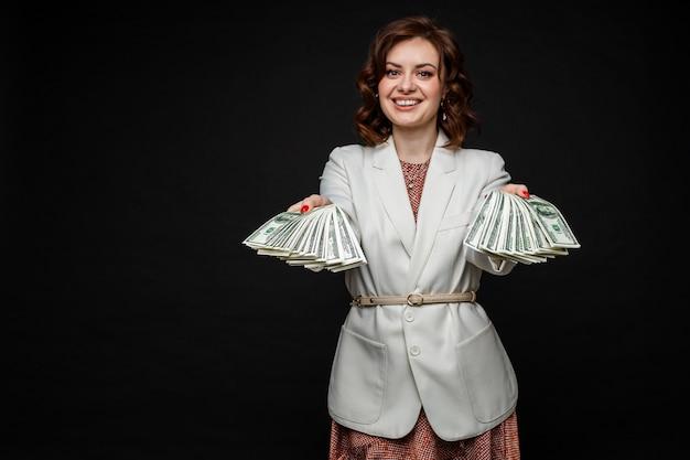 La ragazza carina mostra un sacco di soldi nelle mani, immagine isolata su uno spazio nero