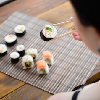 La ragazza castana con le bacchette tiene un rotolo di sushi su un fondo della stuoia di serwing della paglia di bambù