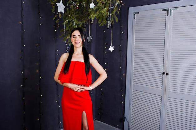 La ragazza castana in vestito rosso ha posato vicino alla decorazione del nuovo anno nella stanza dello studio.