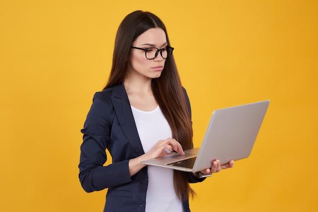 La ragazza castana in vestito sta posando con il computer portatile in vetri.