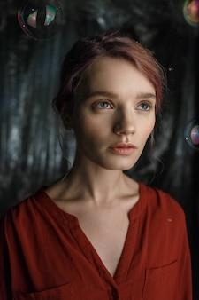 La ragazza caucasica abbastanza giovane in camicia rossa osserva in su. bolle di sapone volano intorno alla sua testa scintillante di colori arcobaleno.