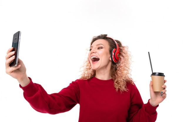 La ragazza caucasica con capelli biondi ricci beve il coffe e fa il selfie, ritratto isolato