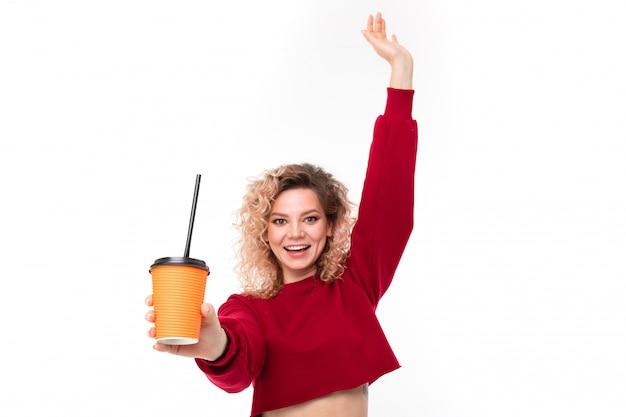 La ragazza caucasica con capelli biondi ricci tiene il coffe e sorride, ritratto isolato