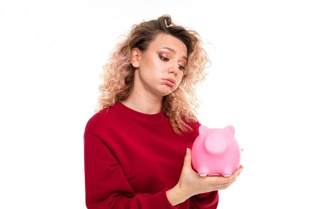 La ragazza caucasica con capelli biondi ricci tiene un salvadanaio rosa del maiale, ritratto isolato su bianco