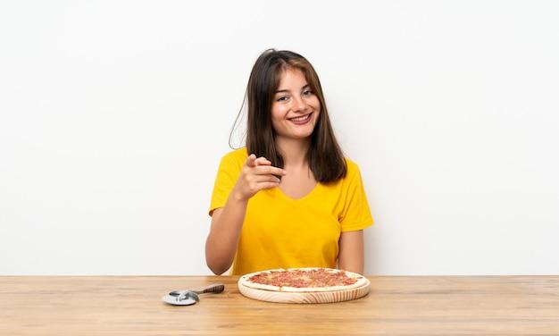 La ragazza caucasica con una pizza indica il dito voi
