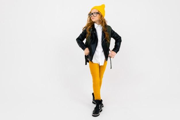 La ragazza caucasica dell'adolescente con il cappello giallo tiene un grande zaino in sue mani isolate su fondo bianco