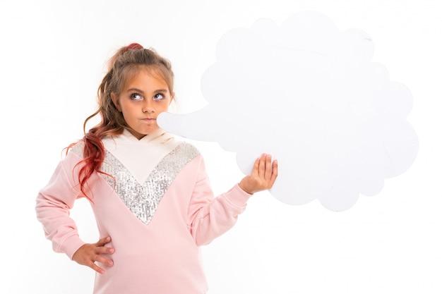 La ragazza caucasica dell'adolescente in felpa con cappuccio rosa gesticola con pensa la nuvola sulla parete bianca