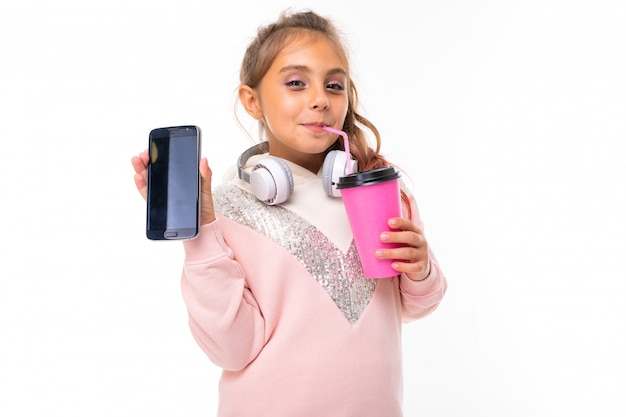 La ragazza caucasica dell'adolescente in felpa con cappuccio rosa gesticola sulla parete bianca