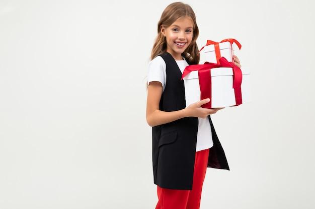 La ragazza caucasica dell'adolescente in rivestimento nero, camicia bianca e pantaloni rossi tiene le scatole bianche con i regali e i sorrisi isolati sulla parete bianca