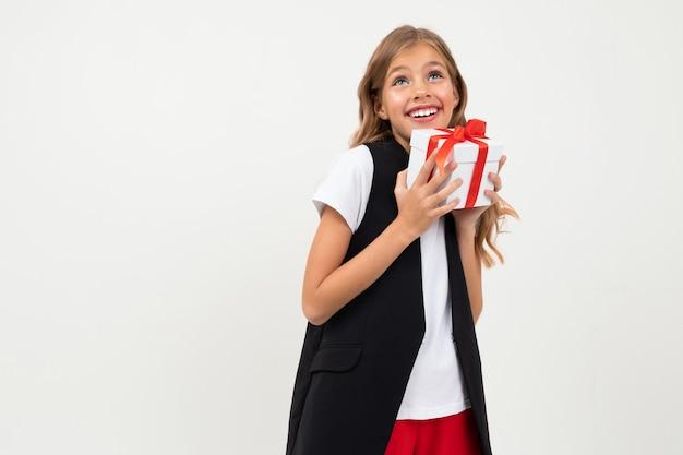 La ragazza caucasica dell'adolescente in rivestimento nero, camicia bianca e pantaloni rossi tiene una scatola bianca con il regalo e sorrisi isolati sulla parete bianca