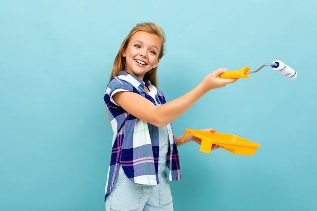 La ragazza caucasica dipinge una parete con un rullo e una pittura isolati su fondo blu