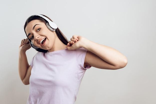 La ragazza caucasica sta ascoltando musica in cuffia
