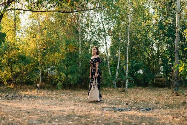 La ragazza caucasica tiene il cliente di tela sul tramonto all'aperto