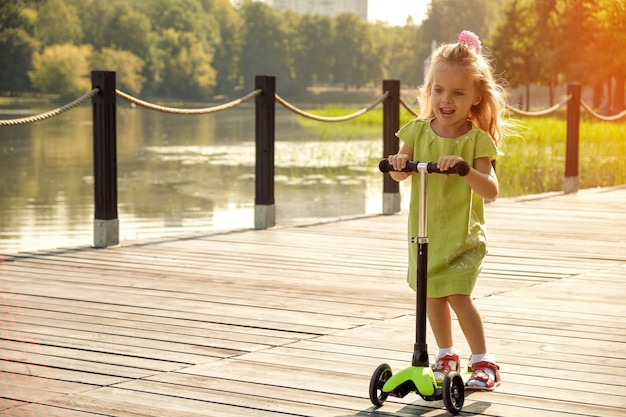 La ragazza cavalca uno scooter nel parco vicino all'acqua. bambino felice, animazione per bambini, bambino attivo.