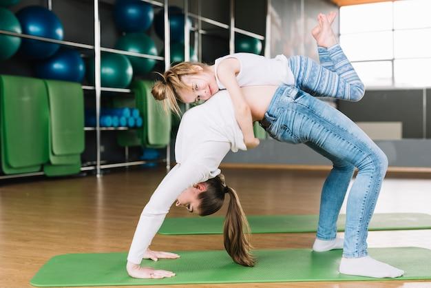 La ragazza che abbraccia la sua madre si esercita sulla stuoia verde di esercizio