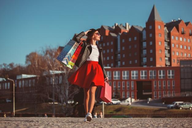 La ragazza che cammina con i sacchetti della spesa sulle vie della città al giorno soleggiato