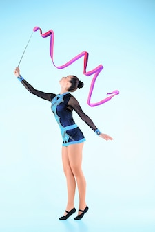 La ragazza che fa ginnastica danza con nastro colorato su una parete blu