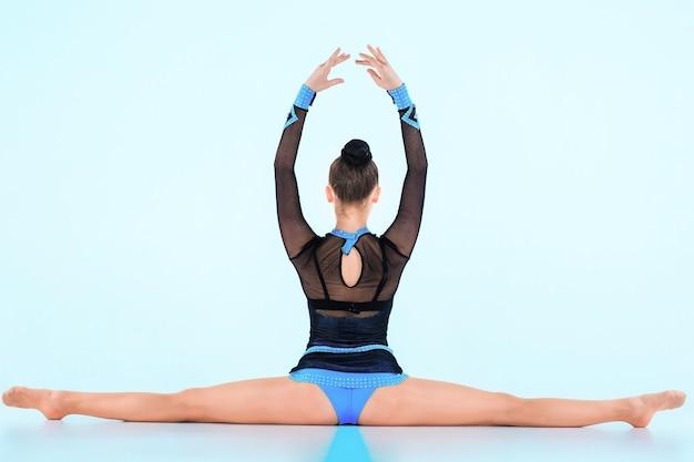 La ragazza che fa ginnastica danza su una parete blu
