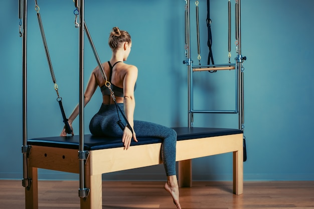 La ragazza che fa i pilates si esercita con un letto del riformatore. bello istruttore esile di forma fisica su fondo grigio del riformatore, scuro, luce di arte. concetto di fitness