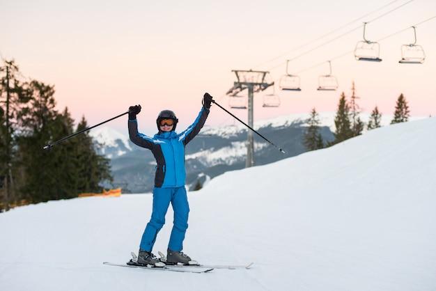 La ragazza che gode della vacanza dello sci che sta sulla montagna nevosa e ha sollevato le sue mani su. donna alla stazione sciistica