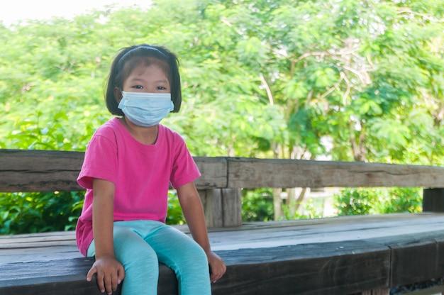 La ragazza che indossa la maschera medica mentre viaggia all'aperto e si siede sul banco