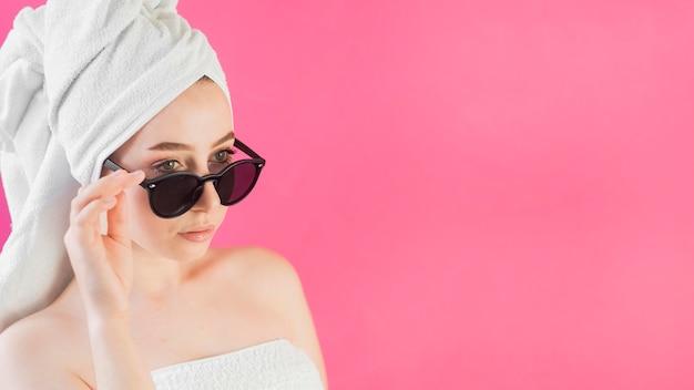 La ragazza che indossa un asciugamano e gli occhiali da sole copiano lo spazio