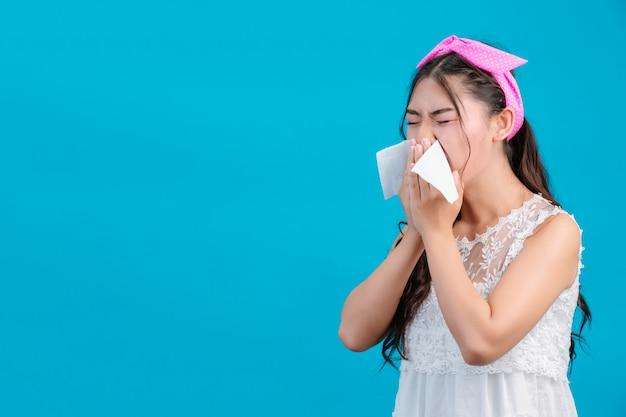 La ragazza che indossa un pigiama bianco non è a suo agio. usando dei fazzoletti per asciugarsi il naso su un blu.