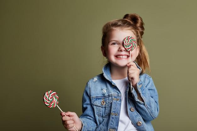 La ragazza che mangia la caramella rotonda lecca la lecca-lecca