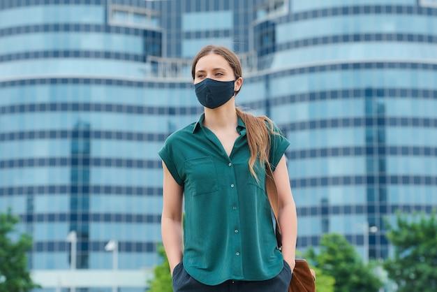 La ragazza che mantiene la distanza sociale indossa una maschera protettiva per evitare la diffusione del coronavirus