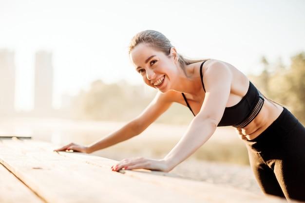 La ragazza che ride fa push up sulla piattaforma di legno